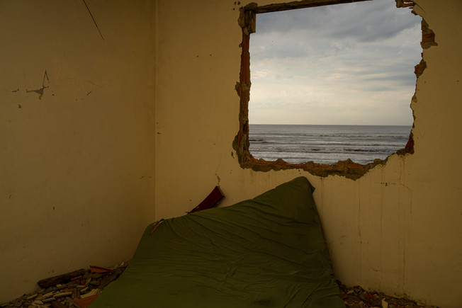 A room with a mattress is seen from inside a destroyed house on East beach in Ilha Comprida, Sao Paulo state, Brazil, February 19, 2020. Before owners abandon their properties, it is common for them to remove tiles, windows, doors and other equipment that can be reused or sold to reduce a small part of their financial losses, knowing that the city has not taken responsibility for the losses claiming that the cause of the damages is due nature's weathering.