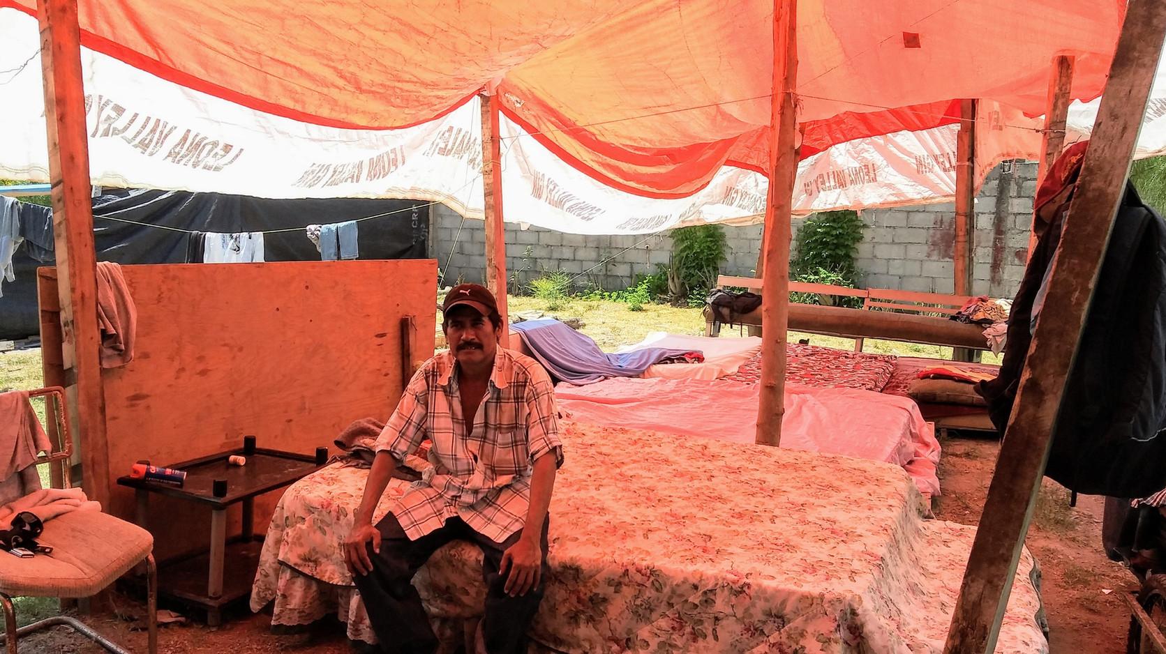 Men sleep outside under tarps