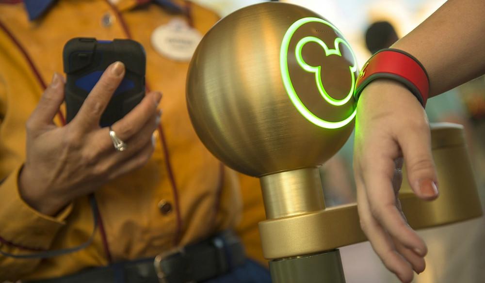 Mão com o Magic Band da Walt Disney World passando na catraca com o contorno do Mickey Mouse para entrar no parque