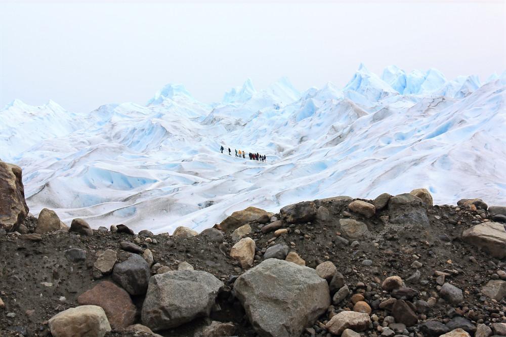 Um grupo de pessoas caminhando sobre o enorme bloco de gelo