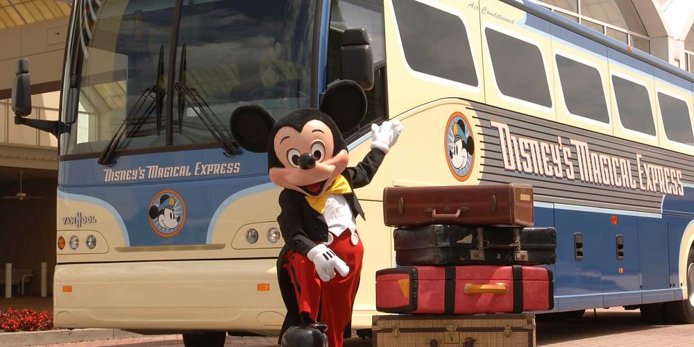 Mickey Mouse, com suas malas, posa em frente ao ônibus em que está escrito Disney's Magical Express