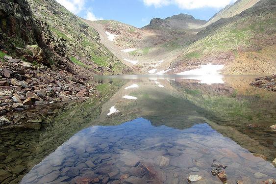 Comapedrosa. Es una ruta semi-circular de poco más de 14 km de longitud que nos conduce al pico más alto de Andorra. El itinerario pasa por diferentes tipos de caminos y senderos. No presenta una dificultad técnica muy alta. Pero la distancia y constancia del camino hacen que sea una ruta destinada a personas que están acostumbradas a caminatas de todo un día y por terrenos de montaña.