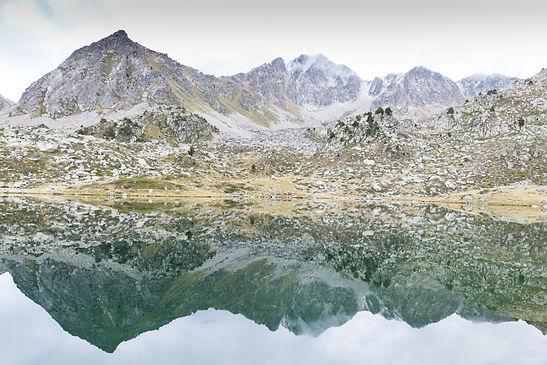 Paisaje con un lago y la naturaleza propia de Andorra. Las rutas y excursiones del Principado te pueden llevar a valles y montañas tan espectaculares como esta. Uno de los rincones que encontrarás en la guía turística Guiand Andorra.