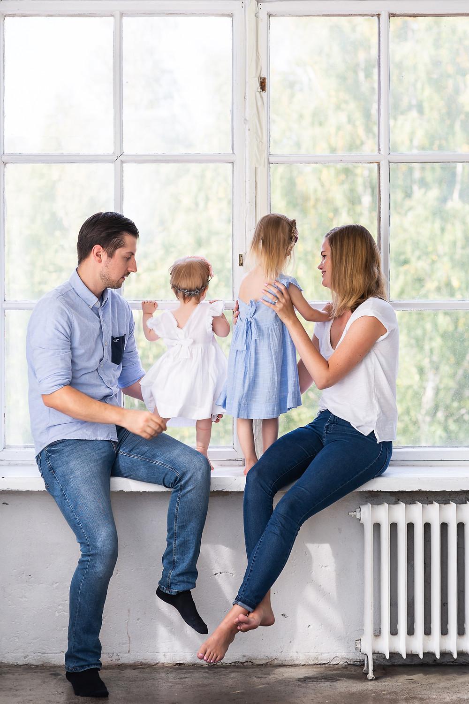 Perhe istuu ikkunalaudalla