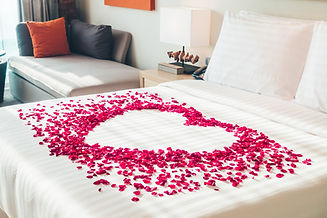 White pillow and Red rose flower on bed decoration in bedroom interior - Vintage Light Fil