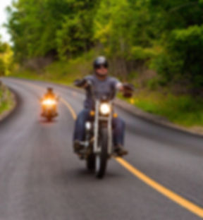 Two friends riding motorcycles on countr
