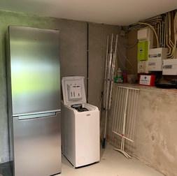 Wasruimte met extra koelkast en diepvriezer