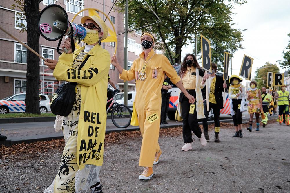 leden van Extinction Rebellion Nederland protesteren met borden en een megafoon