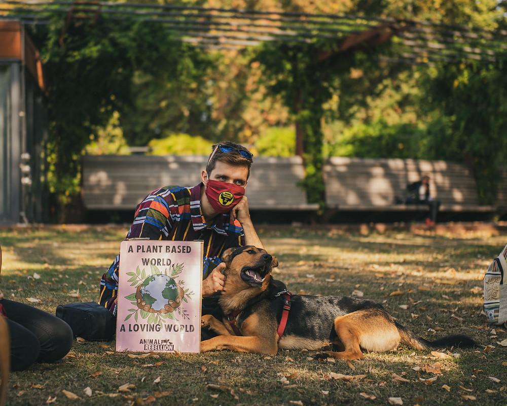 foto van een Animal Rebellion activist met een actiebord en een hond, zittend in het gras.