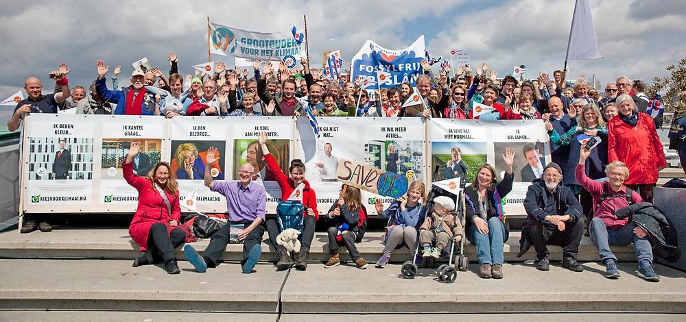 Leden van Grootouders voor het Klimaat poseren met vlaggen en banners
