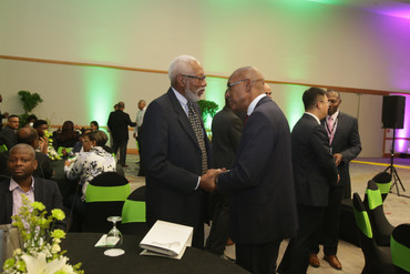 Minister of Public Utilities, Senator Robert Le Hunte, greets Telecom Strategist Selby Wilson before the event begins.