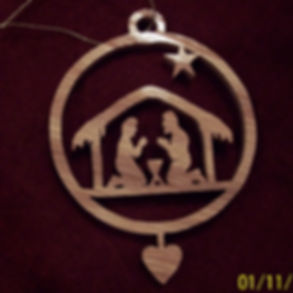 Custom Scroll Art by Joshua Lacey. Joseph and Mary in manger Christmas ornament made from red oak.