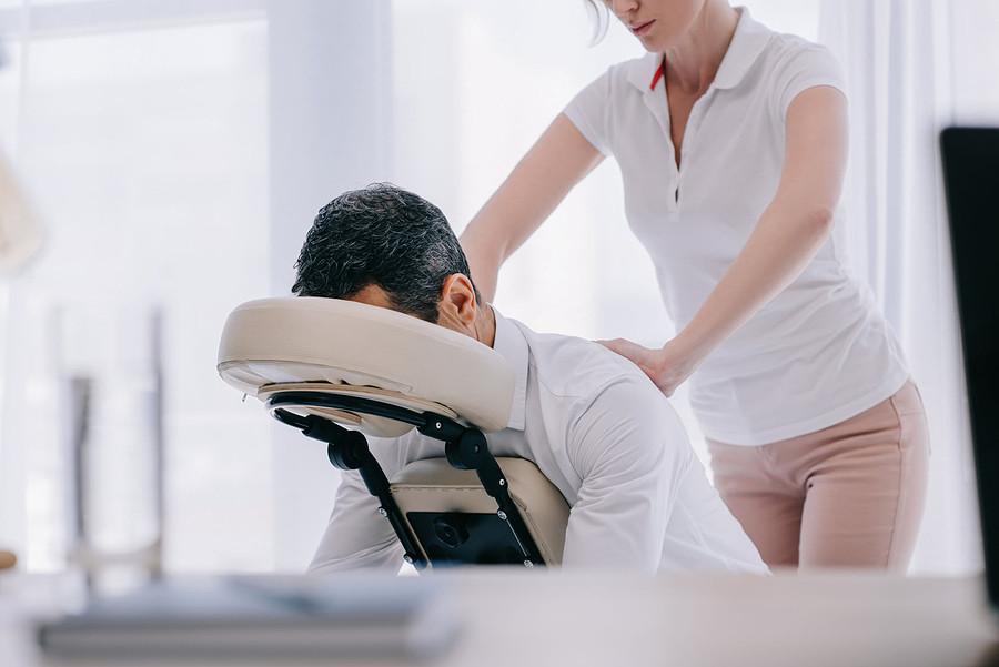 Woman massaging a man's back.
