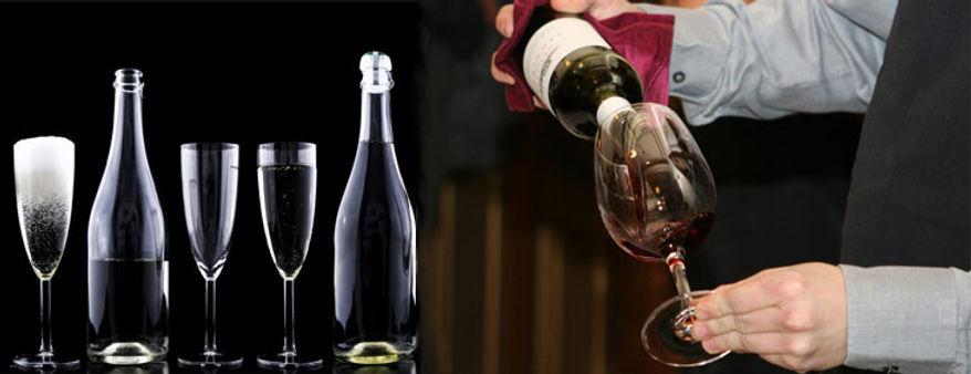 vin rouge versé dans un verre avec bouteilles et verres