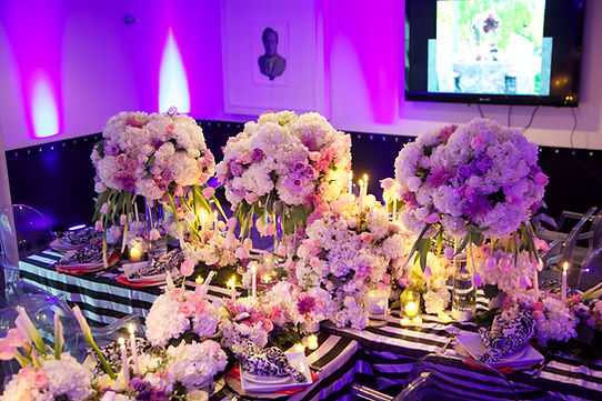 Arial view of tall centerpieces with purple uplights.