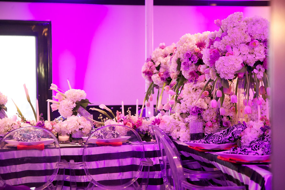 Tall centerpieces and place settings with purple uplights.