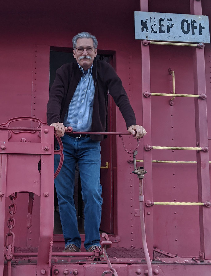 Marcos Smyth, artist standing on a train caboose