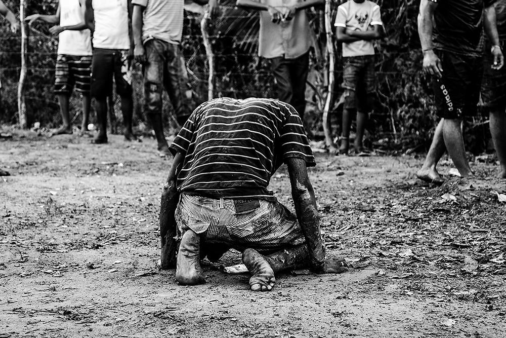 Fotografia de um jovem negro ajoelhado.