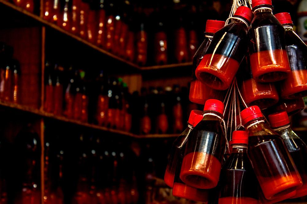 Fotografia de garrafas de azeite de dendê na Feira de São Joaquim, em Salvador/BA.