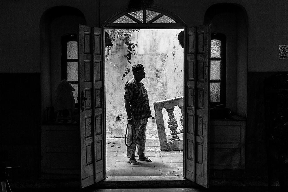 Fotografia de Doté Amilton na porta do barracão do Terreiro Hunkpame Savalu Vodun Zo Kwe.