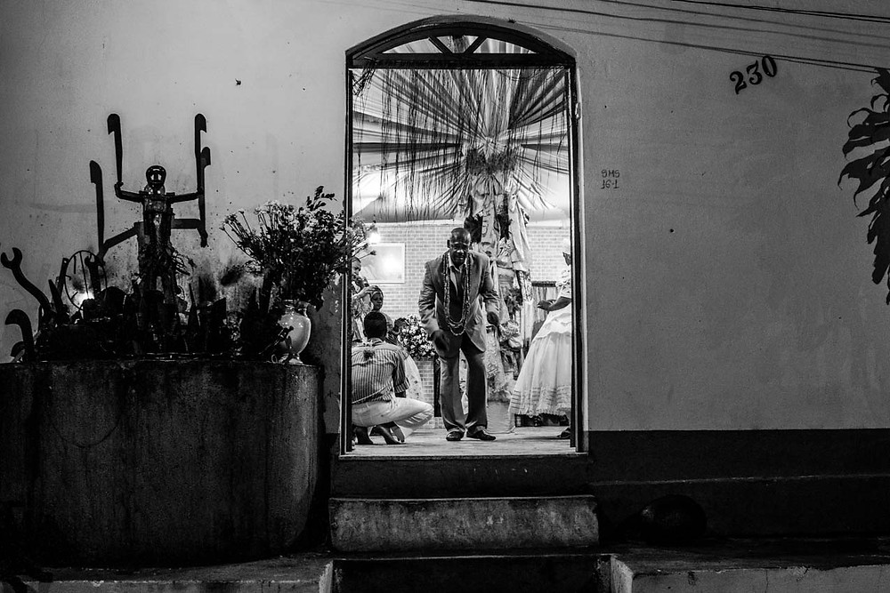 Fotografia do Babalorixá Idelson Sales salvando a porta do Ilê Axé Ogunjá.