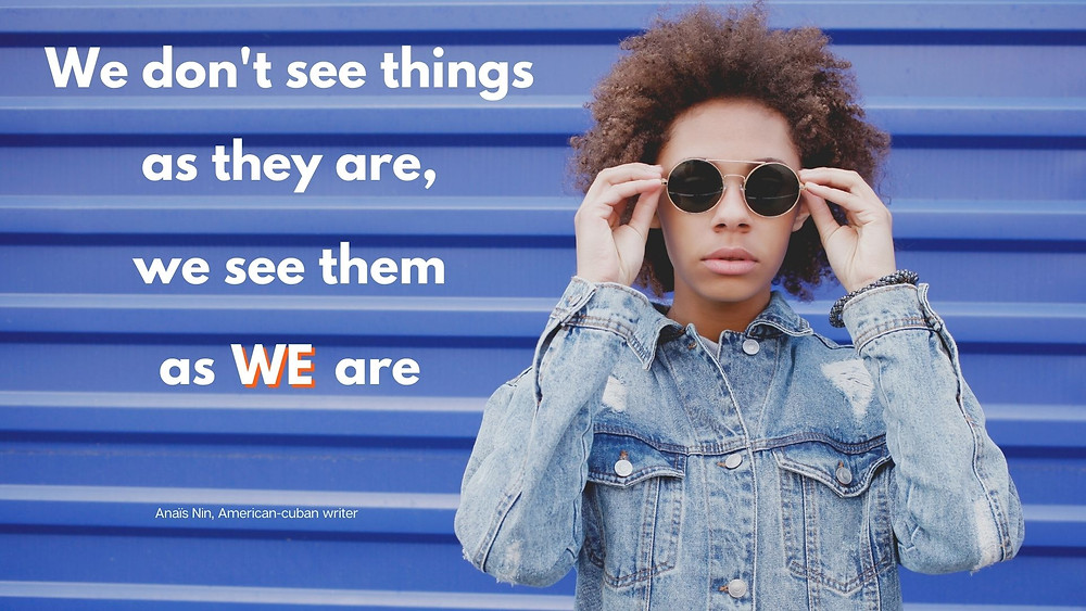 """Image of a person with sunglasses, gently touching the side of the sunglasses, in front of a garage door. On the left side of the image, the sentence reads """"We don't see things as they are, we see them as we are"""", from the American-Cuban writer Anaïs Nin"""