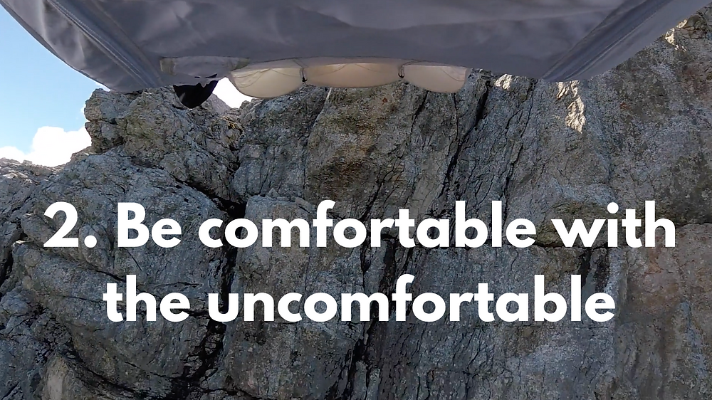 """A photo from a camera pointing down, attached to the neck of a person wearing a cliff jumping suit, showing as the person jumps and flies off the cliff. The text in the slide reads """"2. Be comfortable with the uncomfortable"""""""