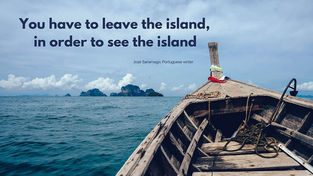 """Image from the inside of a boat in the ocean, with a distant island in the background. On the top left corner, it reads """"You have to leave the island, in order to see the island"""" from the Portuguese writer José Saramago"""