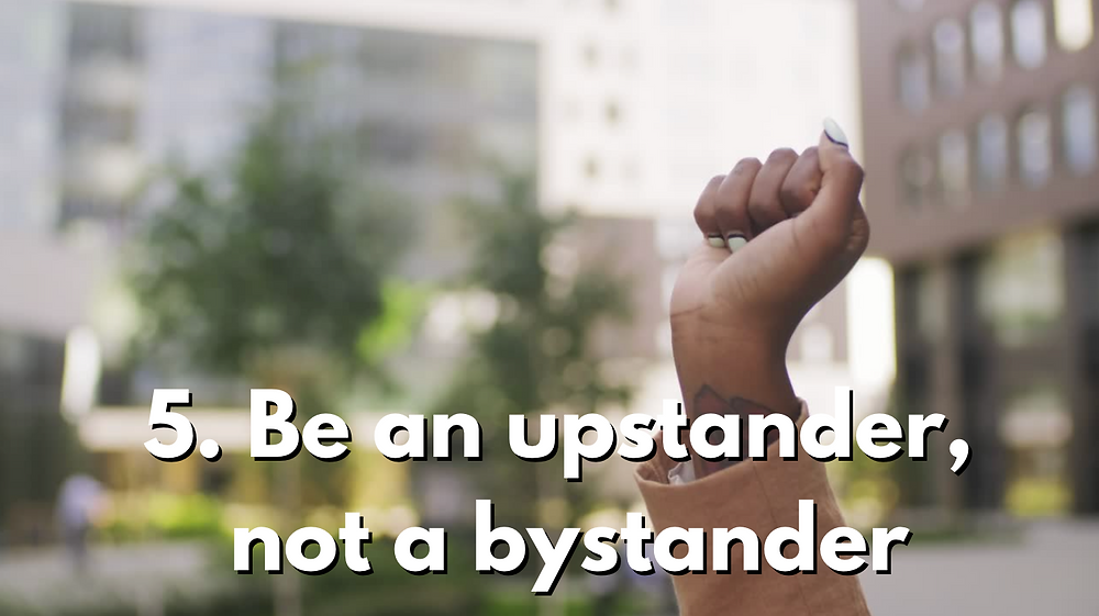 """Picture of an uprisen fist of a woman in an urban landscape and some trees in the background. Background is blurry, focusing on the fist. The text in this slide reads """"Be an upstander, not a bystander"""""""