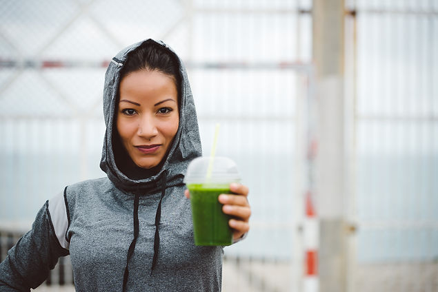 Active woman with healthy green juice.