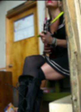 Singer Belinda Blair playing ukulele in a sailor dress.
