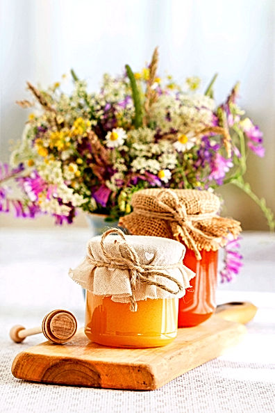 Jars with honey and bouquet of wild flow