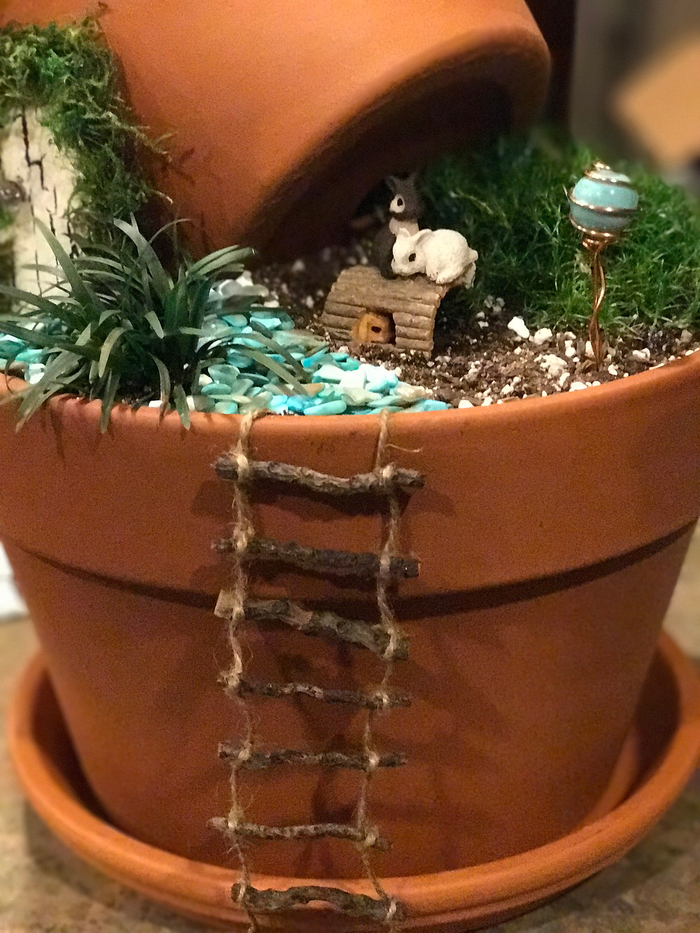 Clay pot fairy garden with ladder, rabbits, gazing ball and door