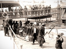 Immigrants arriving by ferry at Ellis Island.