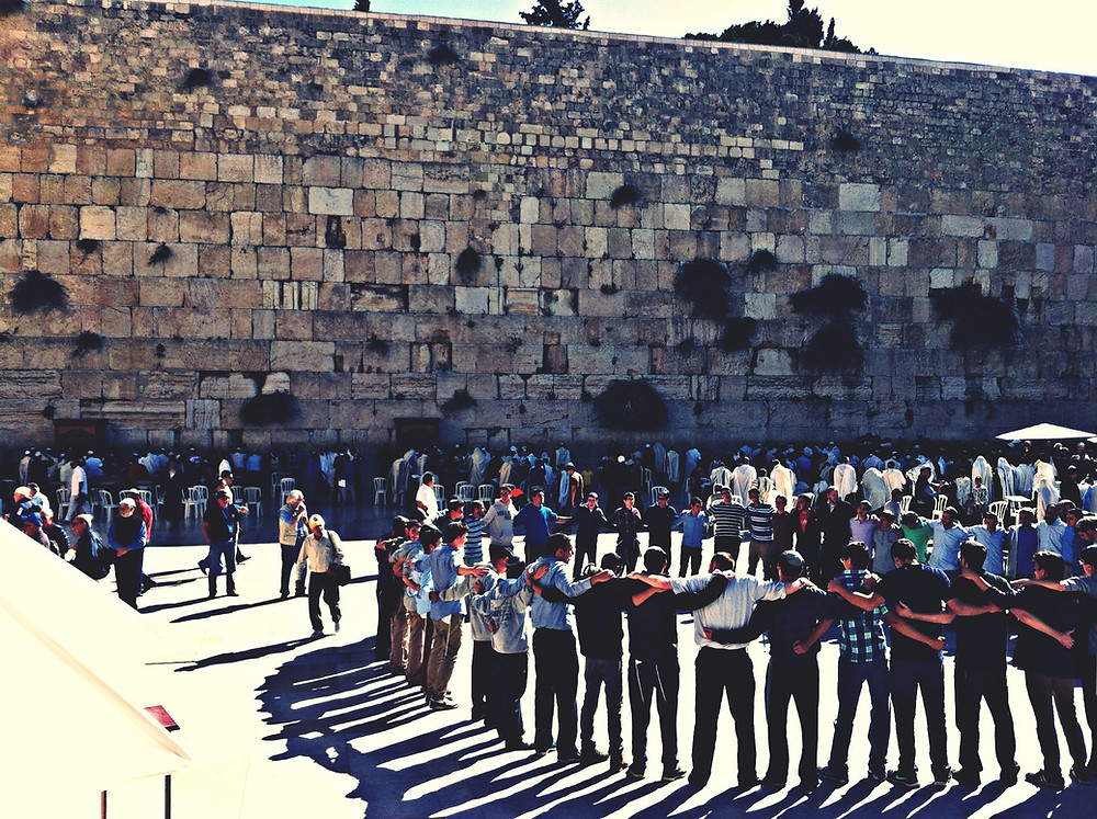 Large group of young men standing in a circle next to the Western Wall in Jerusalem