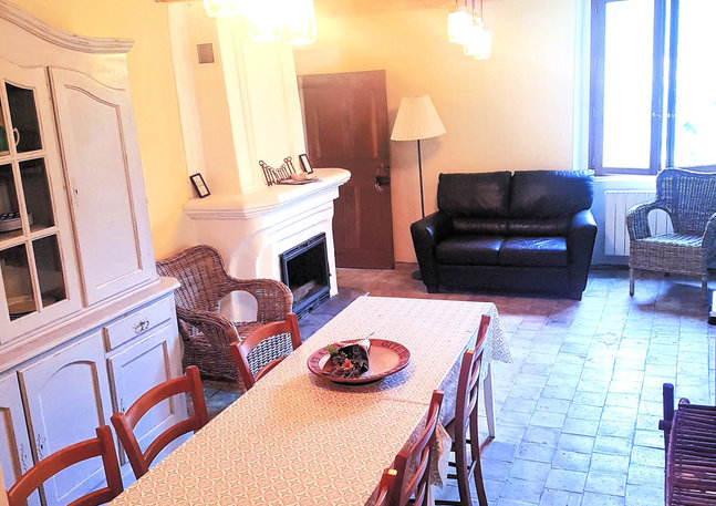 The living room with large dining table and fireplace.