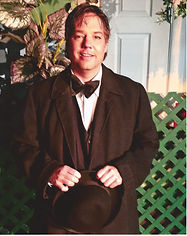 Todd Hanks, the Assistant Editor of Breath and Shadow. He's standing in front of a dark green picket fence. He is wearing a black tuxedo with matching bowtie. His hands are crossed over his abdomen, where he is holding his hat.