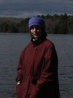 Dorothy Barker, a staff member of Breath and Shadow. She is standing in front of a large body of water. Dorothy is wearing a red coat and blue hat.