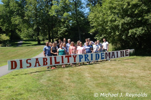 The Disability Right Maine staff behind the Disability Pride Day sign.