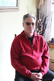 Chris Kuell, the Editor in Chief of Breath and Shadow. He's sitting in a chair while wearing sunglasses, a red sweatshirt, and black pants.