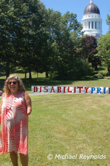 Kim Moody, Executive Director of Disability rights Maine in front of the Statehouse, at Capitol Park. Her left arm is amputated and she has long curly hair.