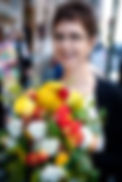 Abigail Astor, a staff member of Breath and Shadow. She's standing behind a large arrange of white, yellow, and red flowers. Abigail has short brown hair and is wearing glasses.