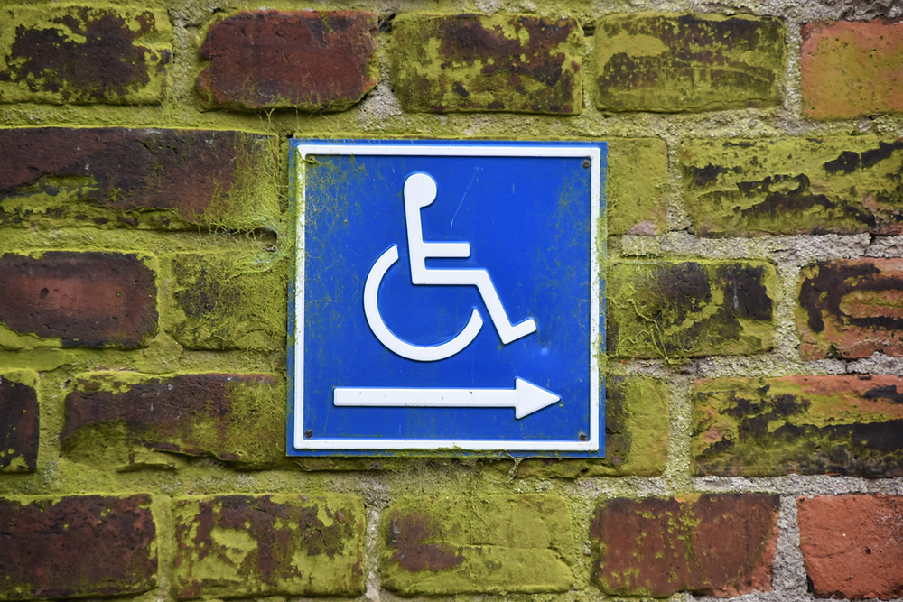 Image of disabled entrance sign on a brick wall