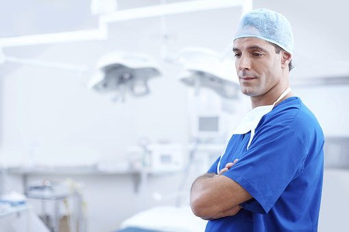 Image Description. A picture of a white, male doctor wearing blue scrubs and a scrub cap. His arms are crossed and he has the look of disapproval on his face. He is standing in a hospital room.