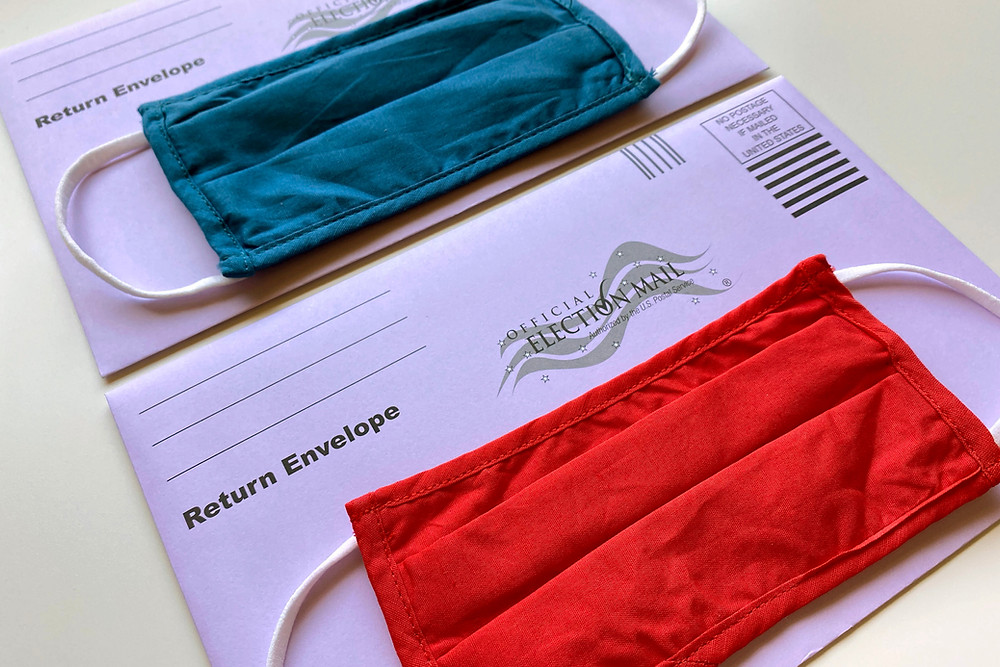 Photo of two white mail in ballot envelopes with two face masks. One mask is blue and the other is red.
