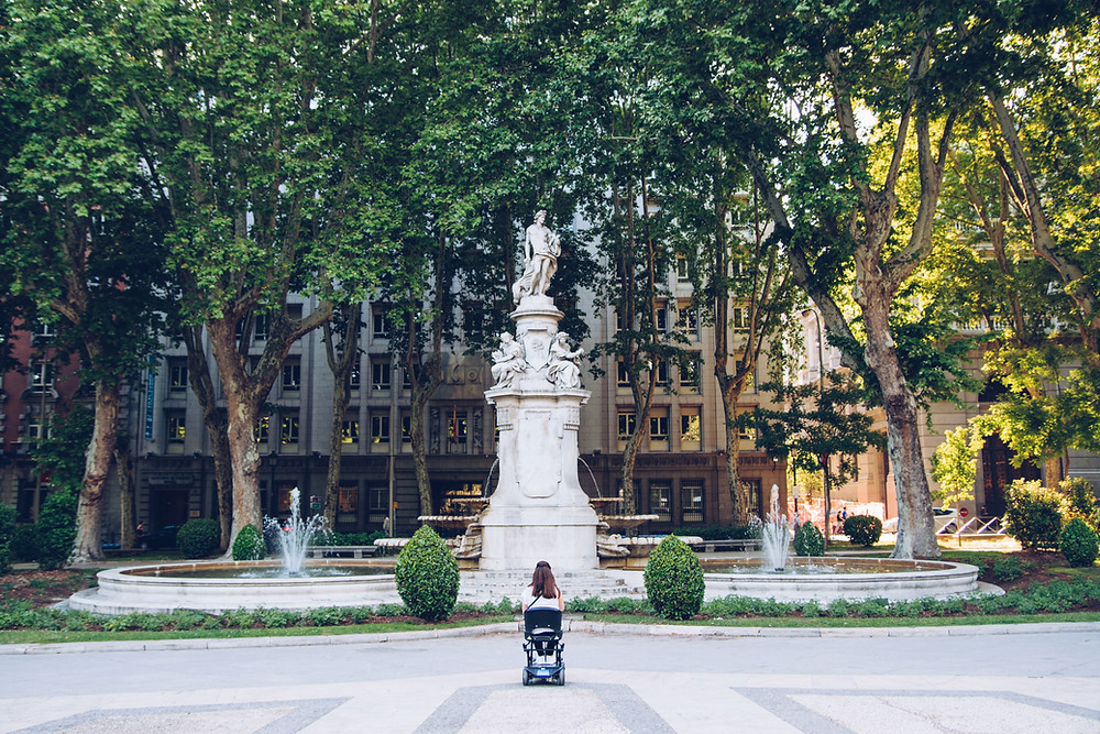 Image of woman in wheelchair looking at a white fountain surrounded by trees and bushes.