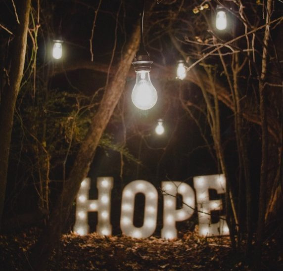 """Image Description: Photo of a light up sign that says """"HOPE"""" in the middle of the woods. There are lightbulbs hanging from the trees and it is night."""