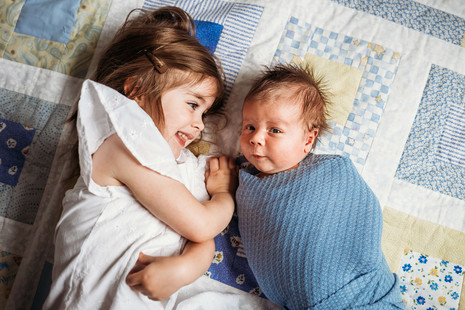 Big sister tickles baby brother on a quilt.