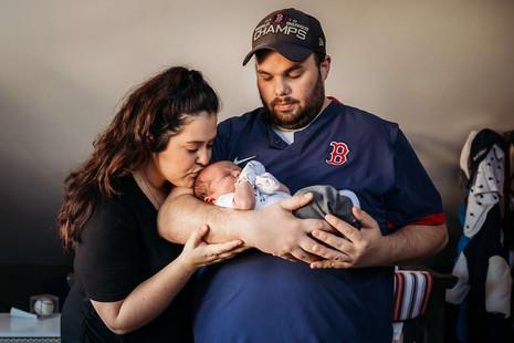 Mom and dad with newborn in baseball nursery in Buffalo.