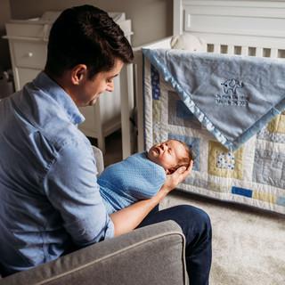 Dad holding baby boy during newborn photos in Buffalo.